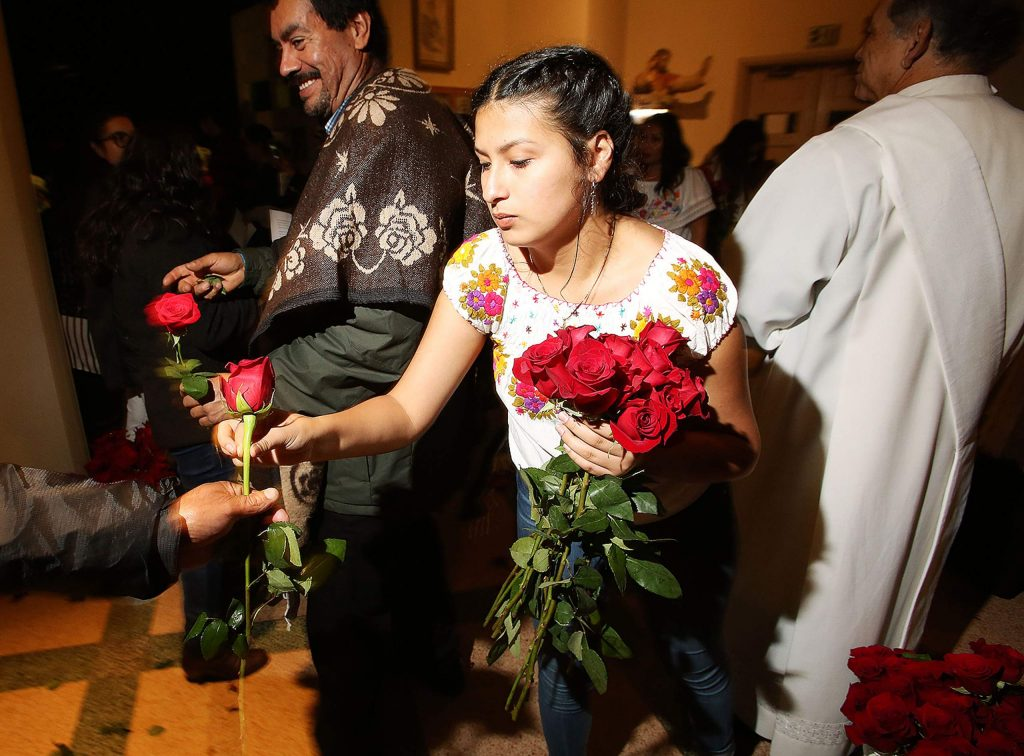 St. Patrick's parishioner Kimberly Mota helps to pass out roses to those attending Thursday evening's mass for Our Lady of Guadalupe.