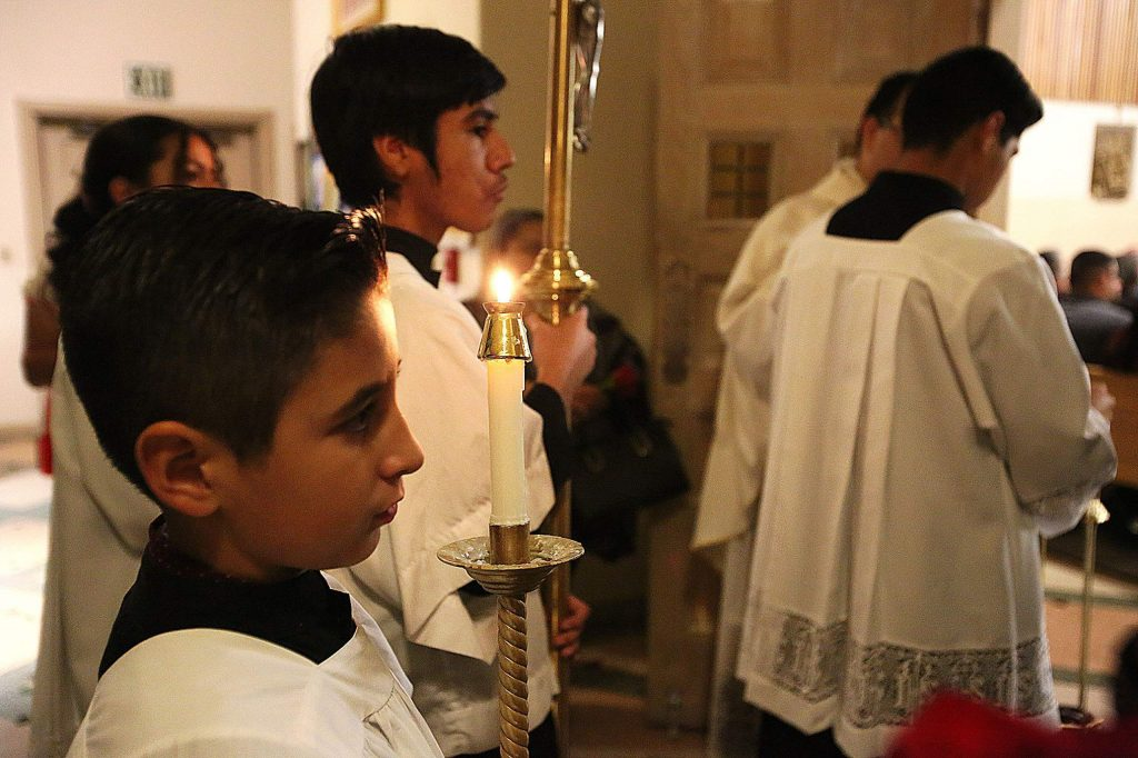 The altar servers await the beginning of Thursday's mass in celebration of the Dia De Guadalupe.