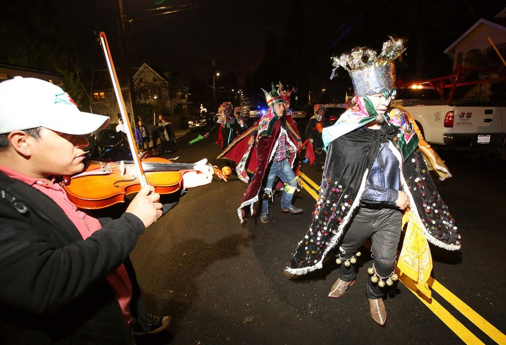 Dancers accompany the tune of a fiddler playing alongside the procession for the Feast of Guadalupe mass Thursday evening along Church Street.