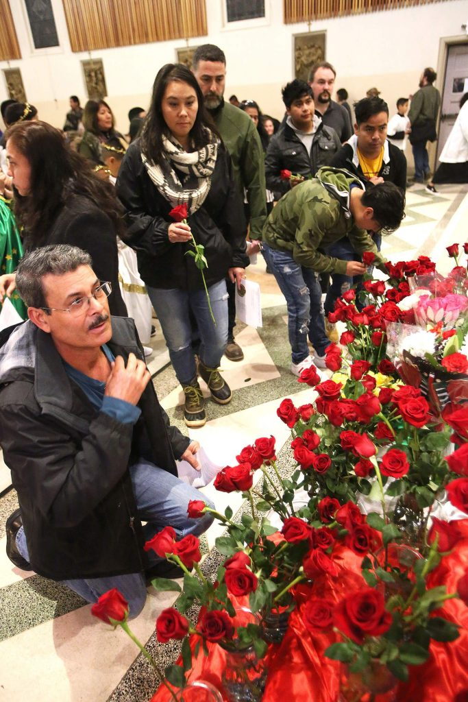 St. Patrick's Catholic Church parishioners genuflect in front of the painting of the Virgen De Guadalupe and place roses in front of her next to the altar.