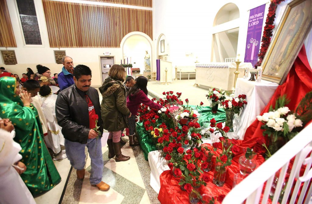 One by one the St. Patrick's Catholic Church parishioners place their roses at the base of a painting of the Virgen De Guadalupe.