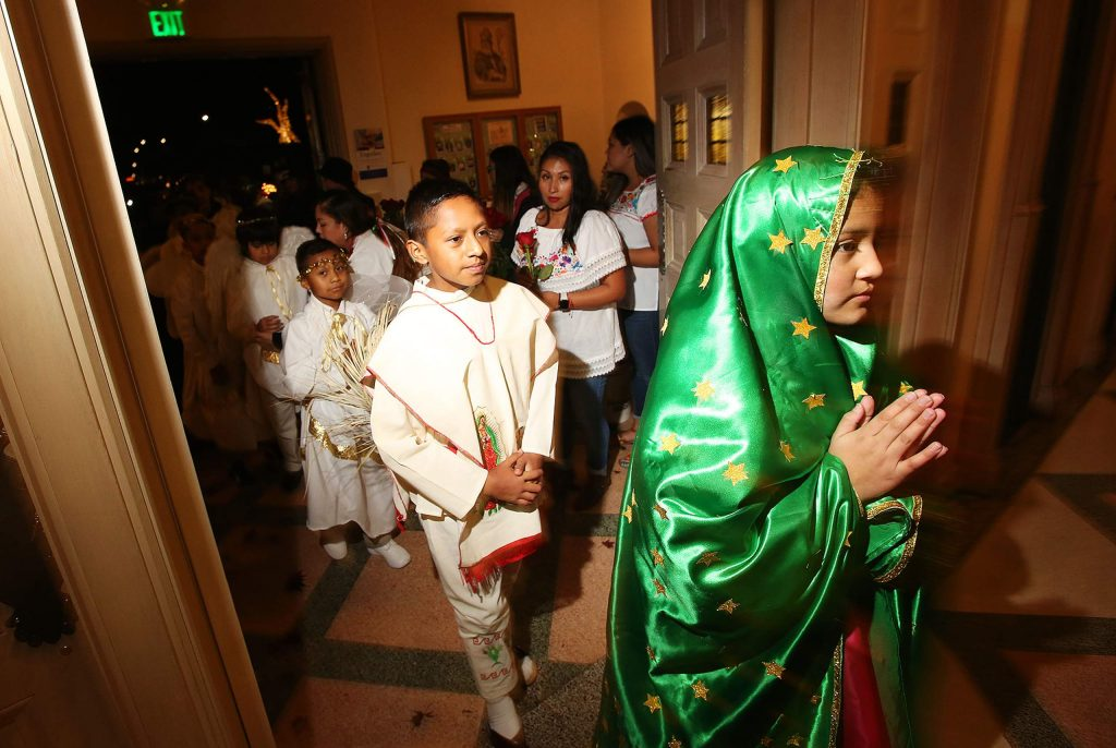 Young St. Patrick's Catholic Church parishioners portraying the Virgen De Guadalupe and angels enter the church after a processional that took place along Church Street in downtown Grass Valley.