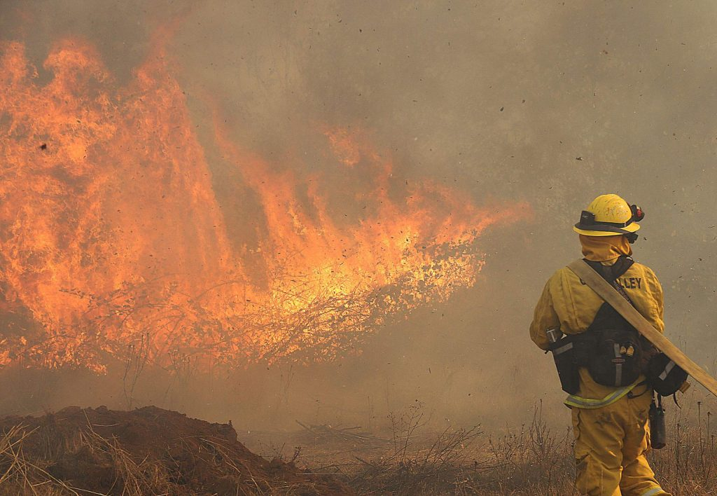 8) A Grass Valley firefighter awaits water to help extinguish a spot fire from the October Dorsey Incident.