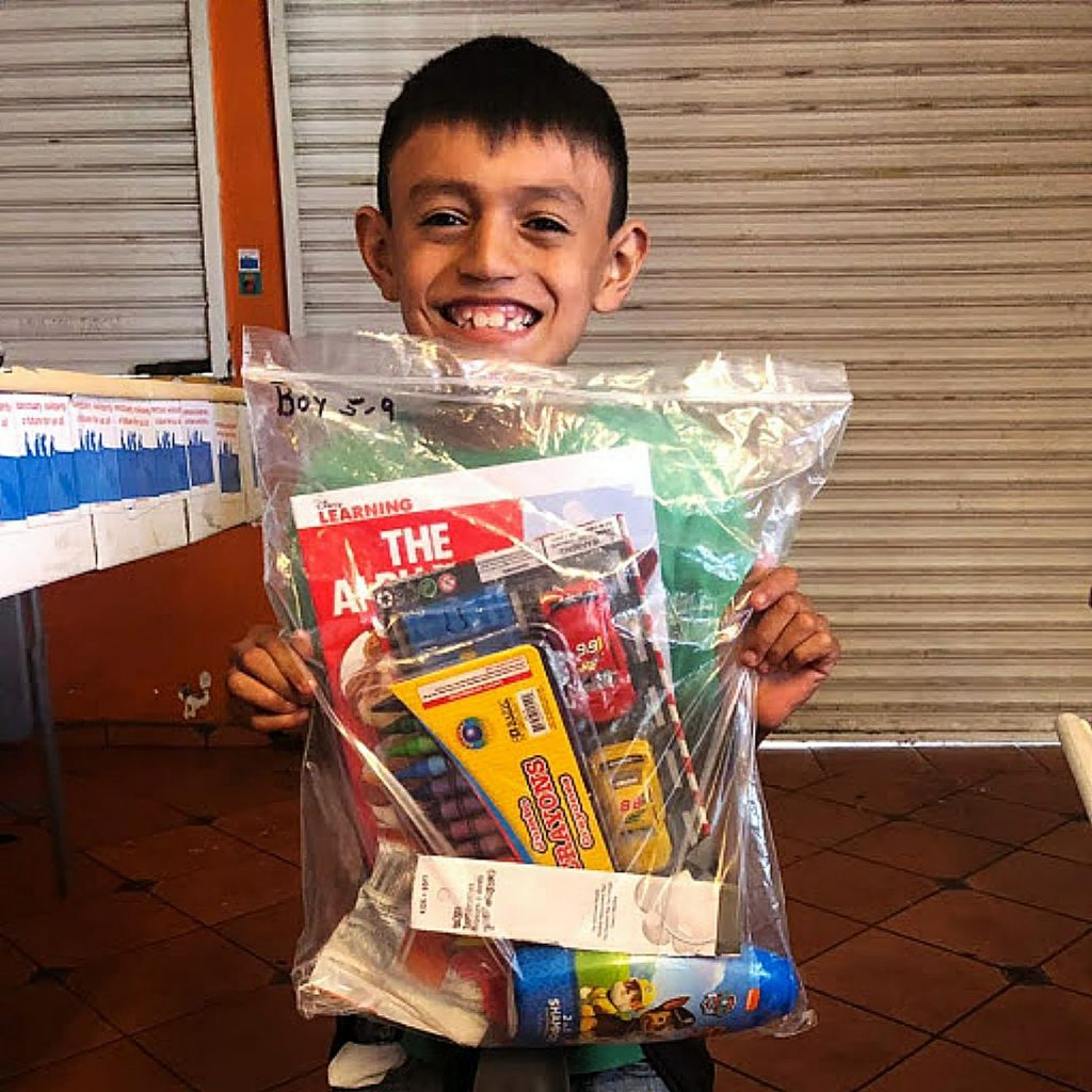 A 7-year-old refugee smiles for the camera after receiving supplies donated by Nevada County residents.