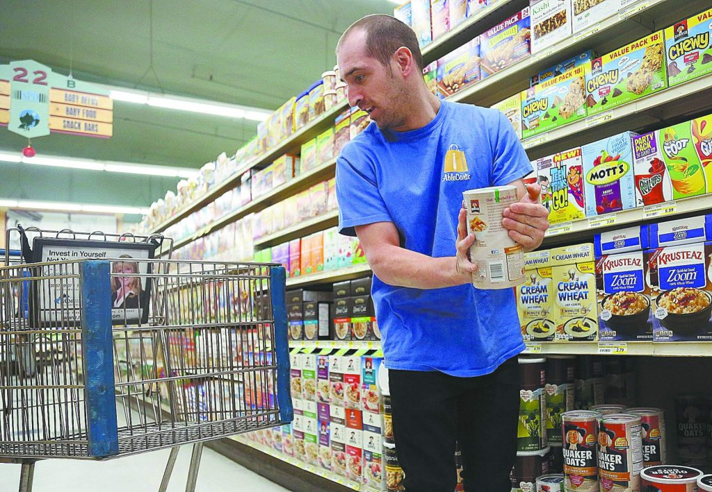 Kevin Szura selects a carton of oatmeal and readies to place it into the cart Tuesday at SPD Market in Nevada City.
