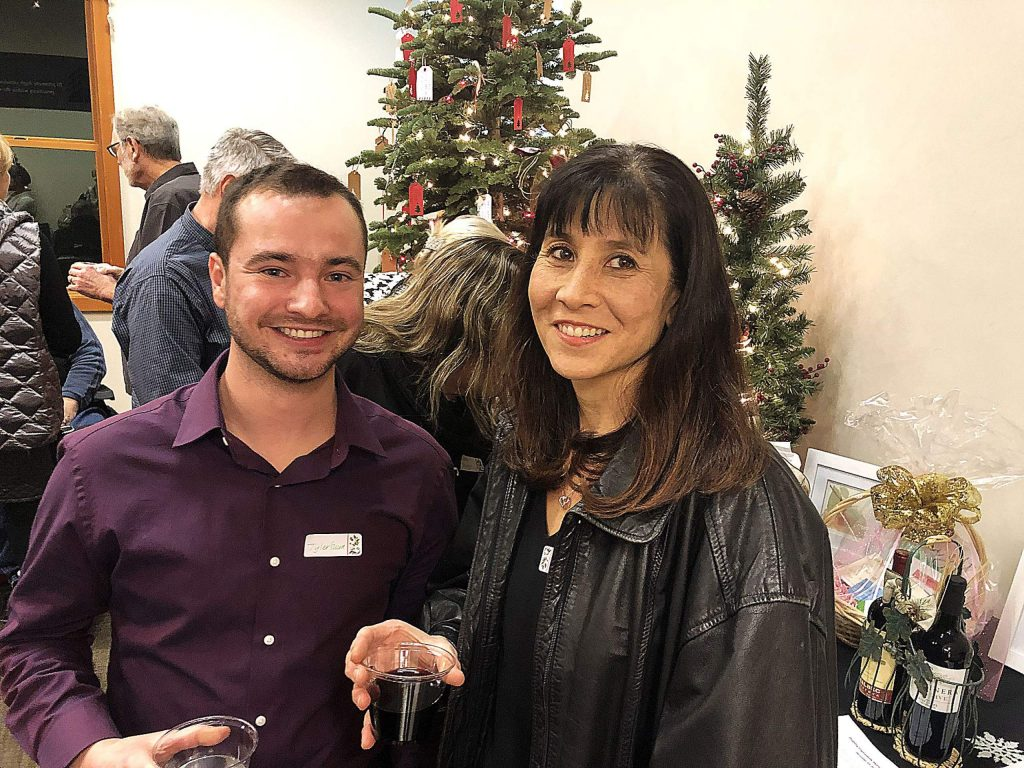 Tyler Szura, founder of tkMomentum, chats with donor and Grass Valley dentist Stacy Fore, right, at tkMomentum's holiday fundraiser on Dec. 10.