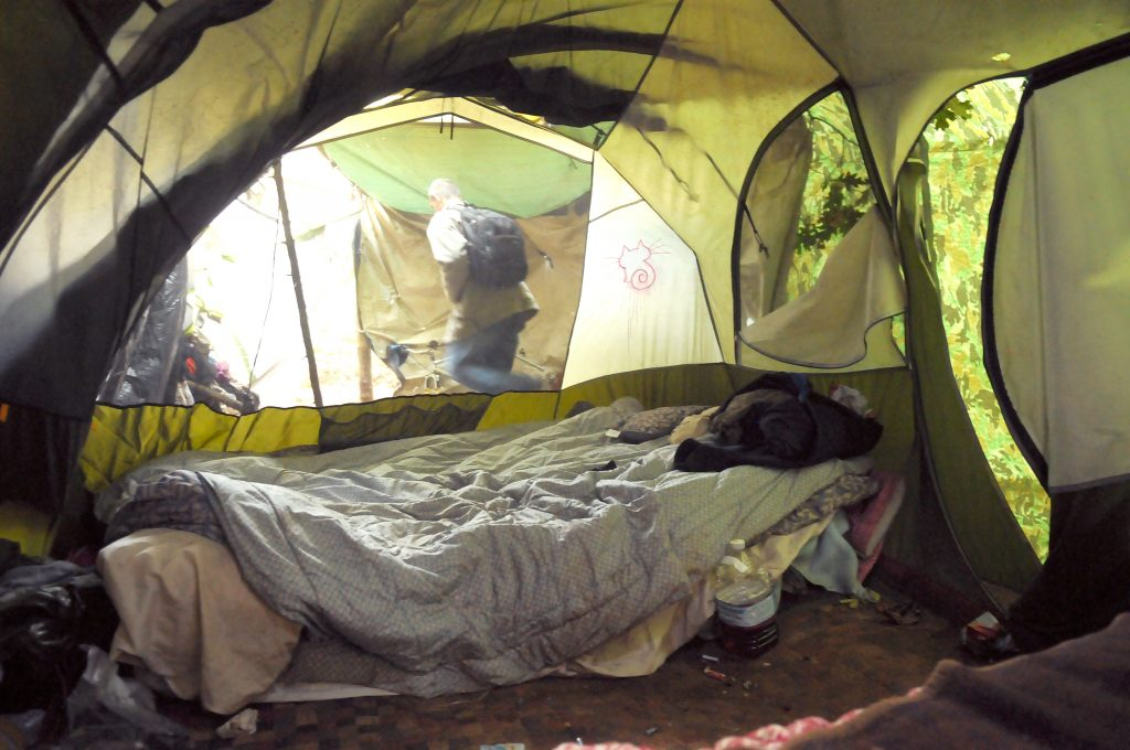 A western Nevada County homeless man leaves his 16-foot by 8-foot tent surrounded by camouflaged tarpaulins in order help keep him dry and warm when staying out in the forest at night.