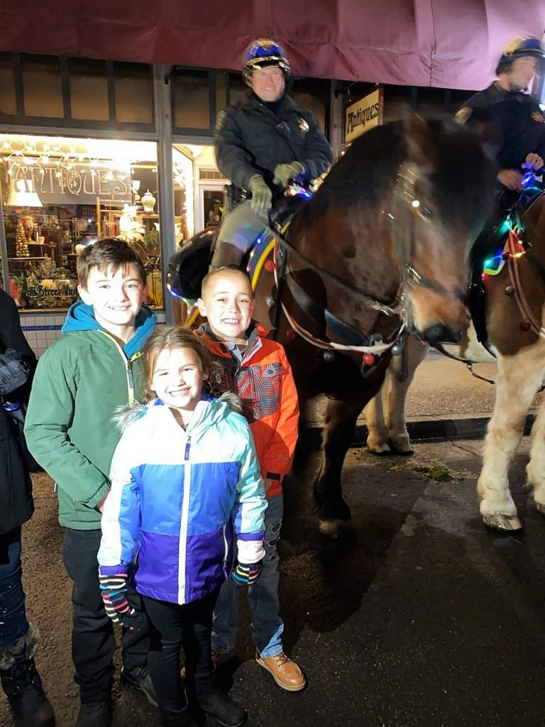From left, Ten-year-old Kane Byrd, five-year-old Addison Byrd, and eight-year-old Conner Elder were just a few of the Cornish Christmas revelers who posed for photographs with the California Highway Patrol Clydesdales.