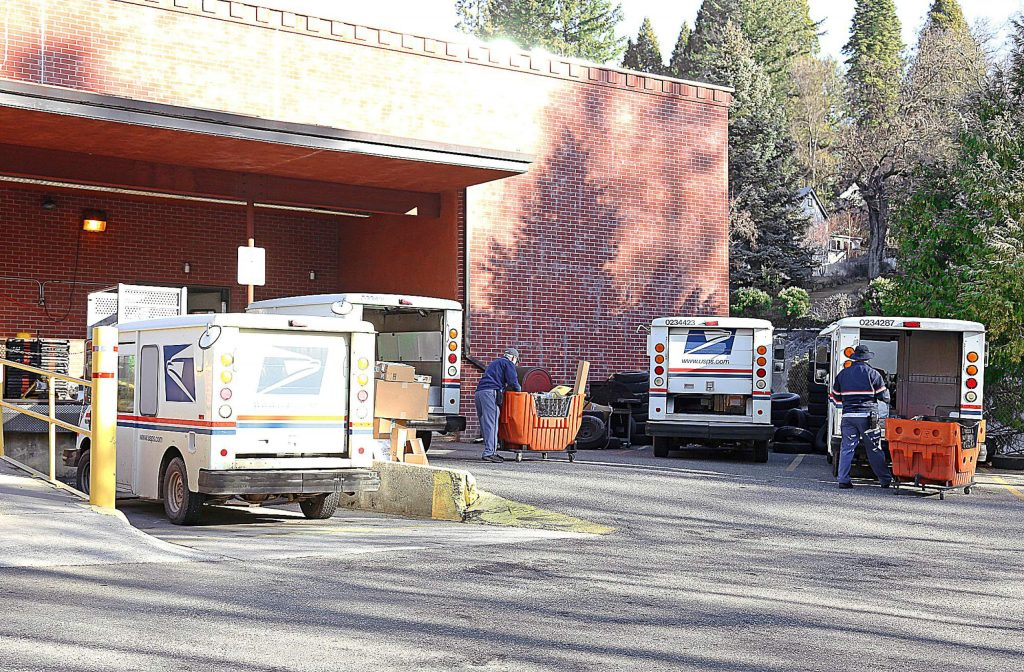 Mail carriers load their trucks Friday morning at the Nevada