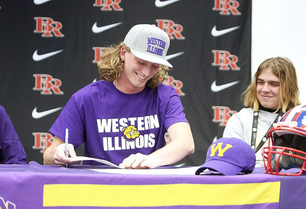 Bear River High School's Tre Maronic smiles as he signs his letter of intent to play D-1 college football for the Western Illinois Leathernecks Wednesday in front of about 70 people.
