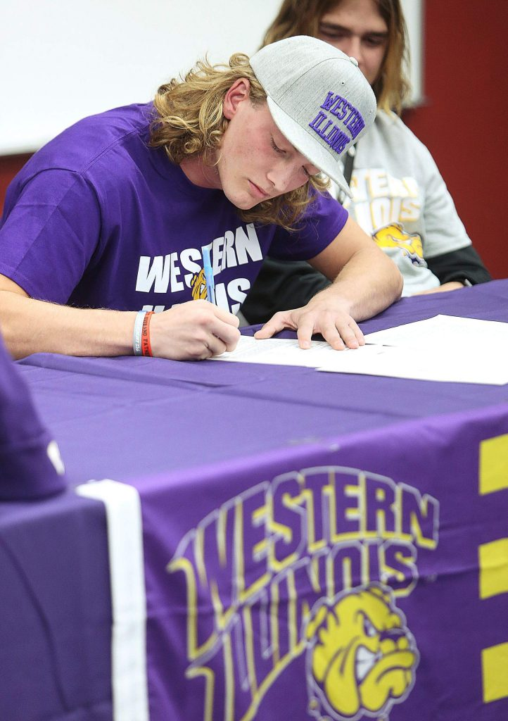 Tre Maronic signs his letter of intent to play college football for Western Illinois Wednesday in front of about 70 friends, family, and school administrators at Bear River High School.