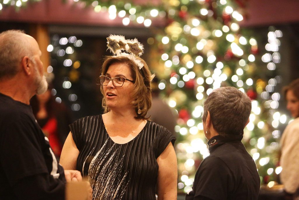 Alta Sierra Country Club board member Sandy Laffins mingles with New Years Eve dinner attendees as they file in Tuesday evening.