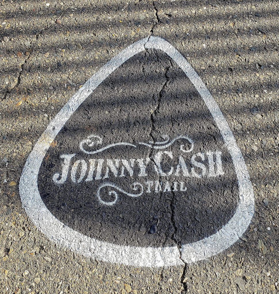 A guitar pic sign can be seen along the trail.