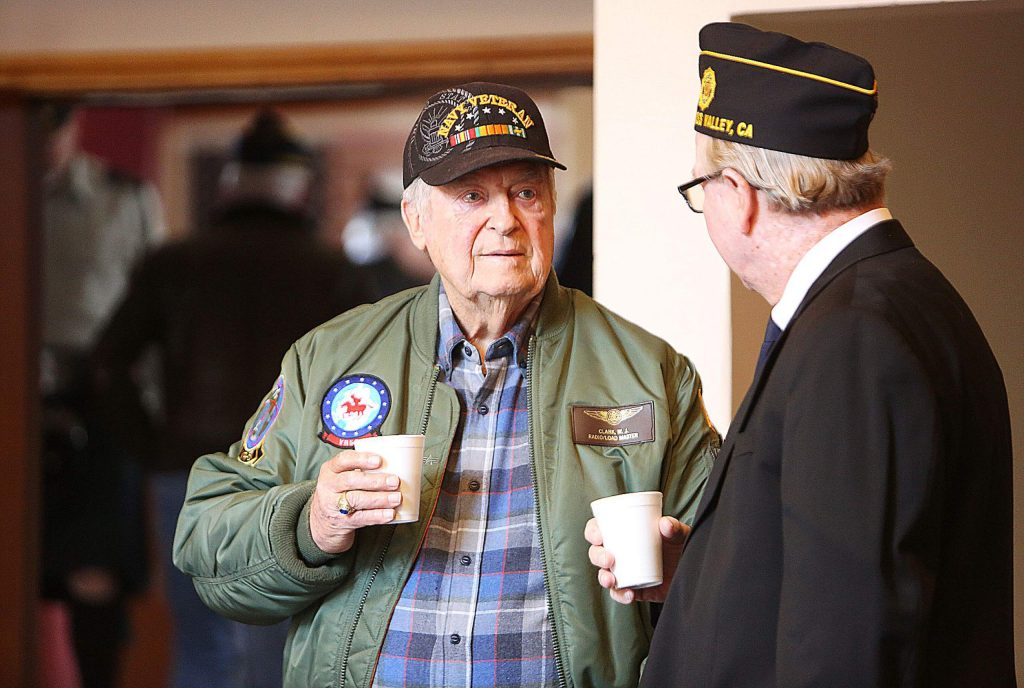 The U.S. Navy's Bill Clark takes some time to mingle with other vets over coffee and donuts prior to Saturday's Pearl Harbor Day ceremony.