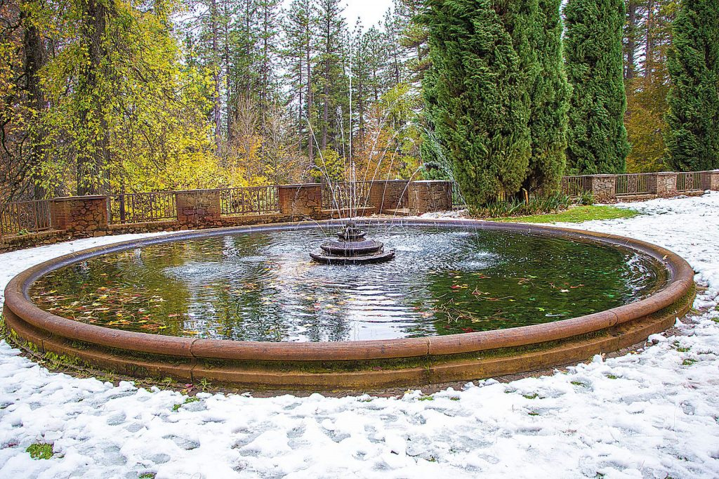 Seasons changing - fall leaves in the fountain, surrounded by snow.