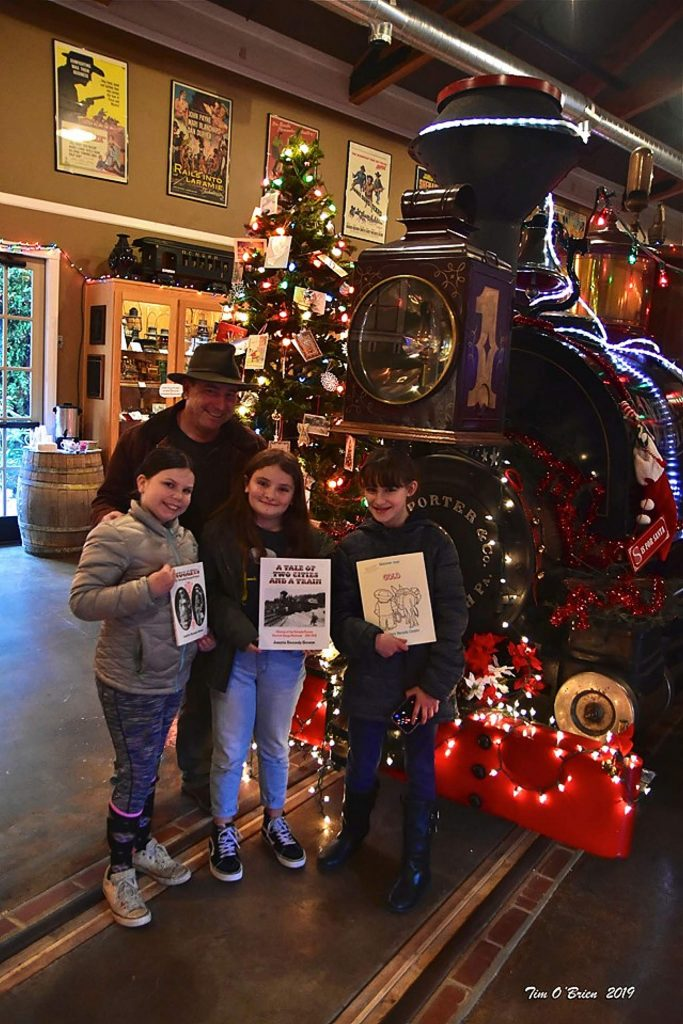 Juan Browne poses with his daughter and friends, and the remarkable writings of his Mom, Juanita Kenedy Browne at Christmas at the Railroad Museum.