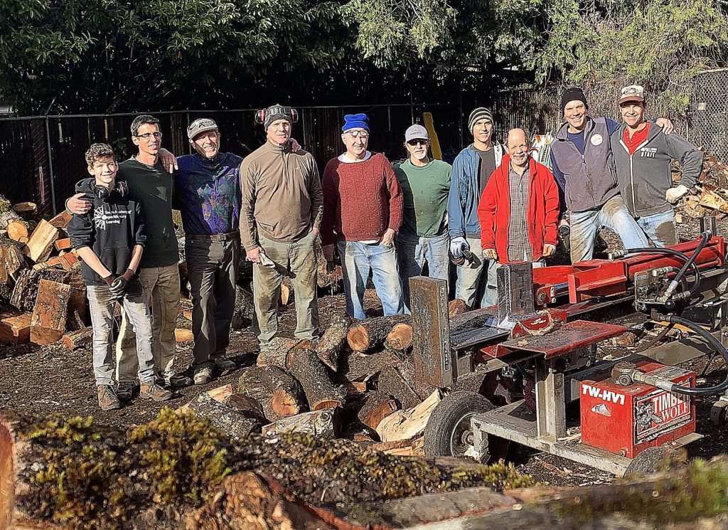 Volunteers for Gold Country Community Services, and men from the ManKind Project, splitting firewood.