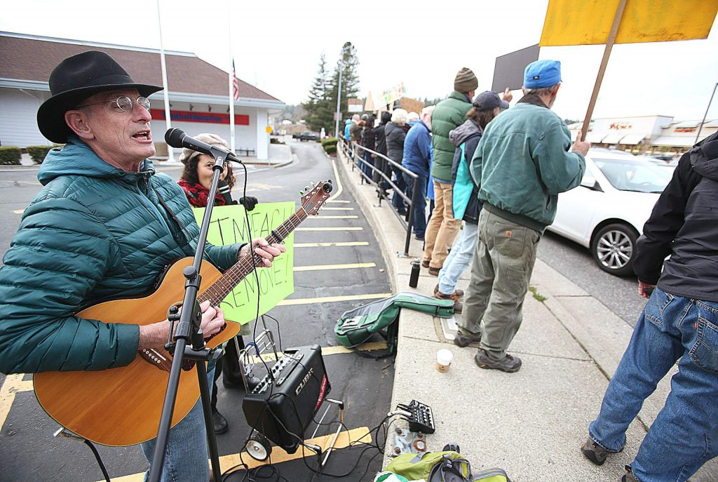 Jeffrey Gottesman and Prema Joy Robins of the band Justice for the Peace play the guitar and sing songs along with those gathered along Brunswick Road at Sutton Way Tuesday afternoon.