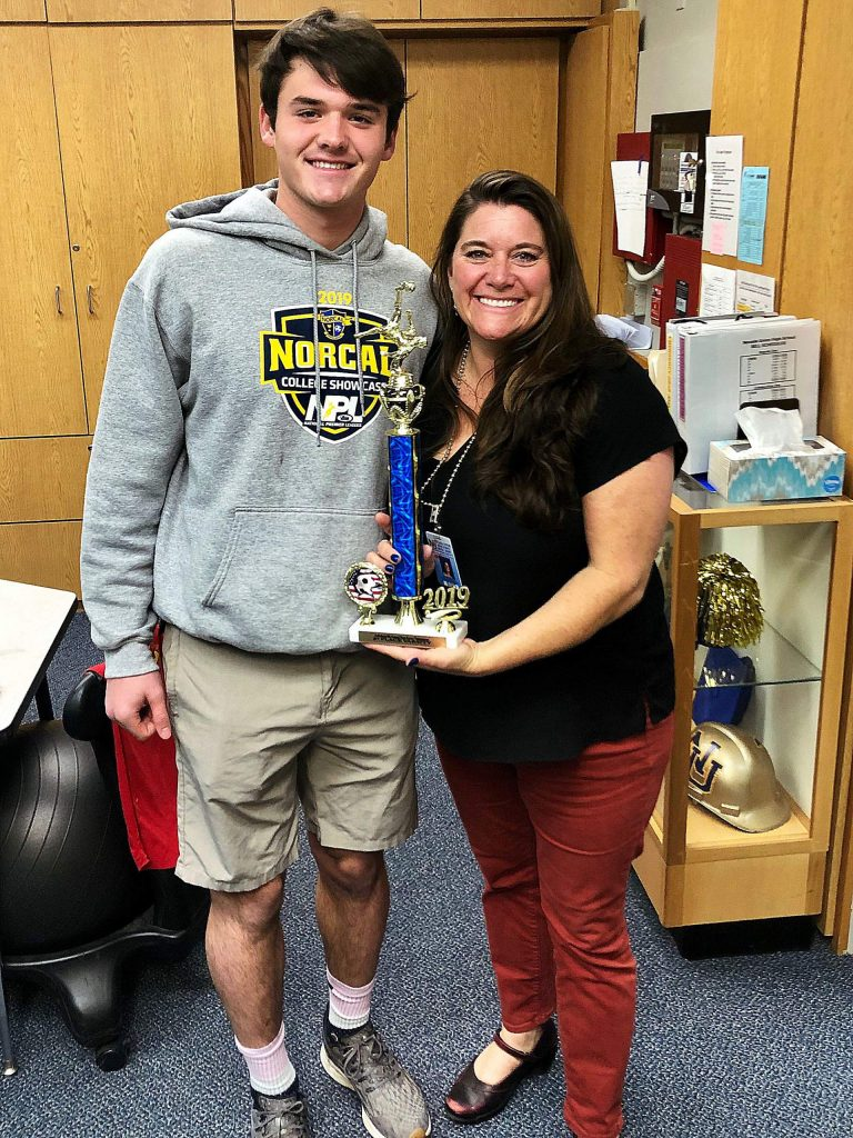 Nevada Union's Steven Person presents NU Principal Kelly Rhoden with the trophy.