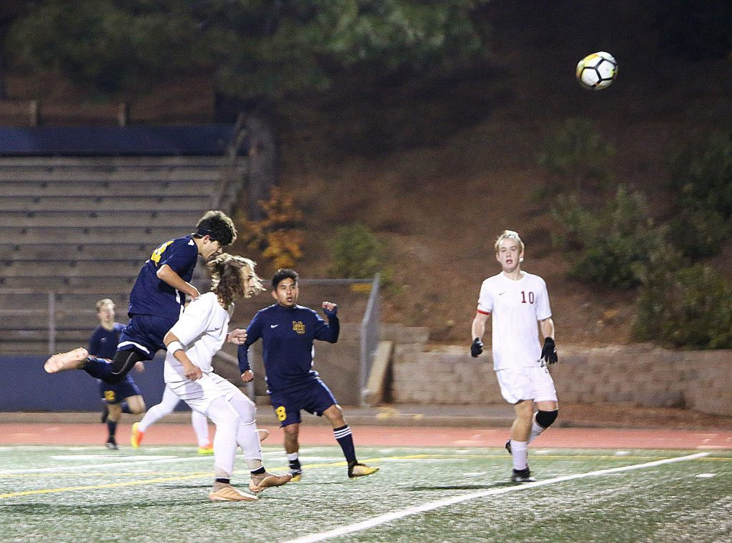 Nevada Union High School's Isaiah O'Connell (14) heads in one of his scores on goal during Tuesday's match against the Bear River Bruins.