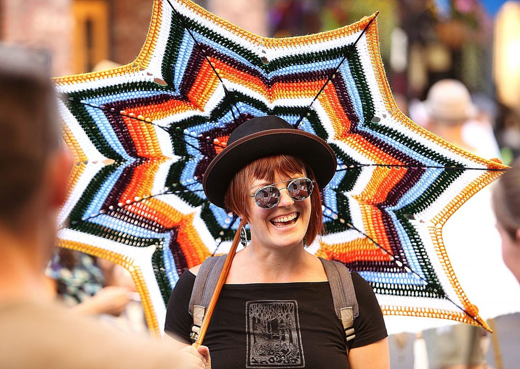 2) Kelly Patton reacts as she meets friends at the Make Local Habit booth on Pine Street during the final Summer Nights of the 2019 season. She is holding a parasol made by local artist Lord Von Schmitt.