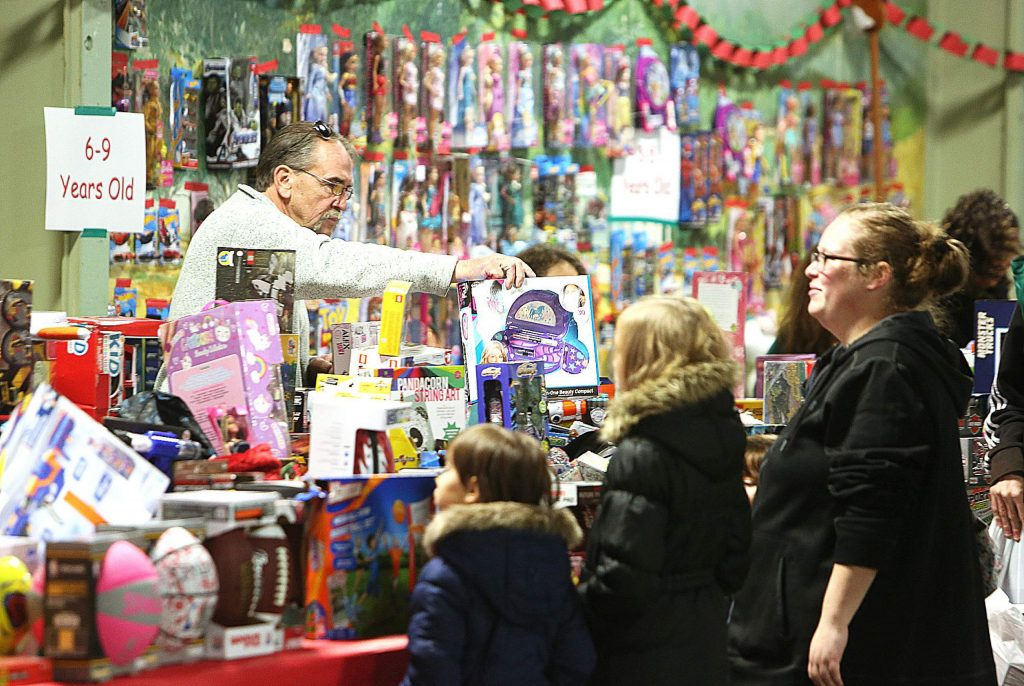 Children and their families are helped by volunteers to find their favorite toy during Saturday's food and toy giveaway at the fairgrounds.