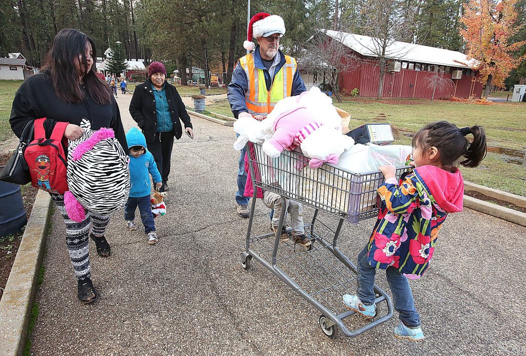 A happy family is helped out to the parking lot by volunteer John Brusher with their food and toys from the annual Food and Toy Run.