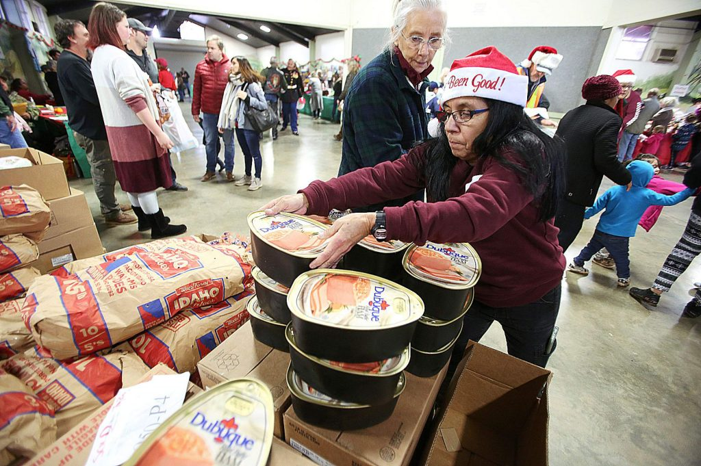 First time volunteer Brenda Espino helps hand out hams, turkeys, and sacks of potatoes to families during the annual Food and Toy Run Saturday at the Nevada County Fairgrounds.
