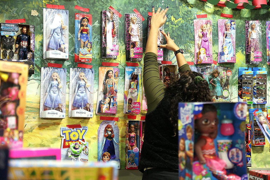 Barbies of all types are pasted to a wall for the young girls to see as they decide which gift to take following Saturday's Food and Toy Run at the Nevada County Fairgrounds.