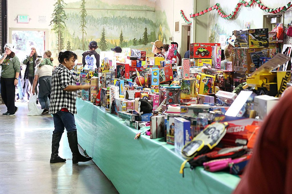 Volunteers organize the thousands of donated toys dropped of by the motorcyclists prior to the gift giveaway Saturday afternoon at the Nevada County Fairgrounds.