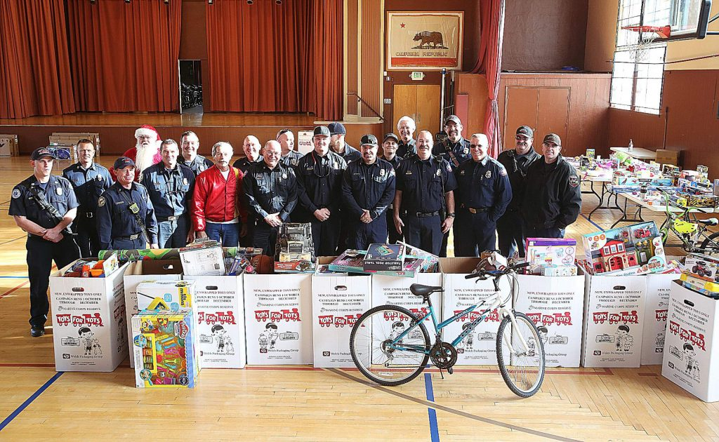 Area firefighters stand behind boxes of toys collected from their fire stations and donated to the local Toys for Tots giveaway.