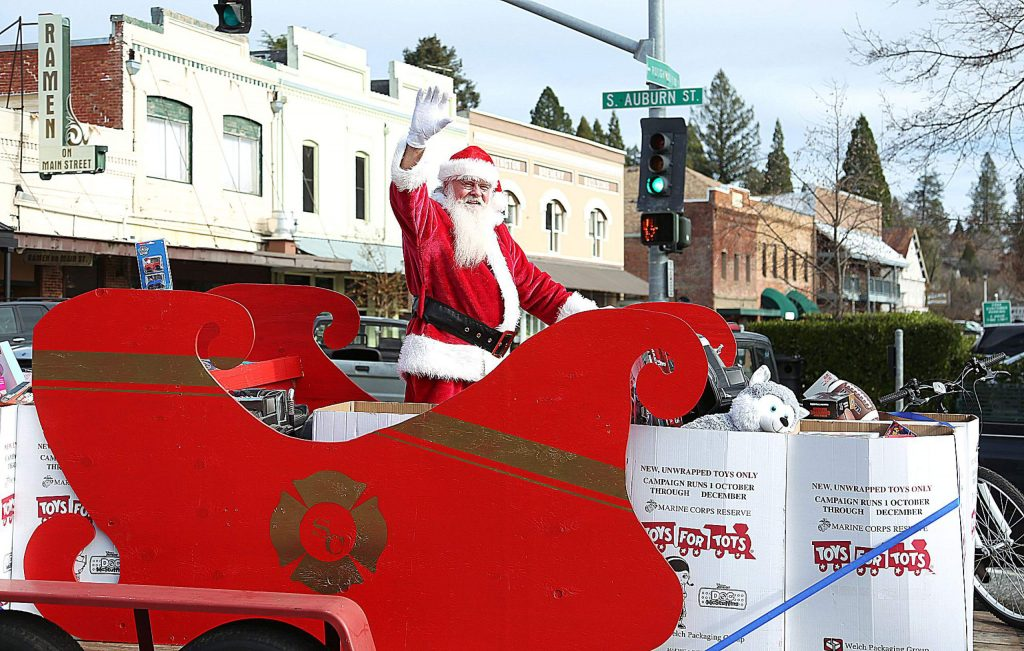 Santa waves from his sleigh being led through the streets of downtown Grass Valley by firefighting and police vehicles.