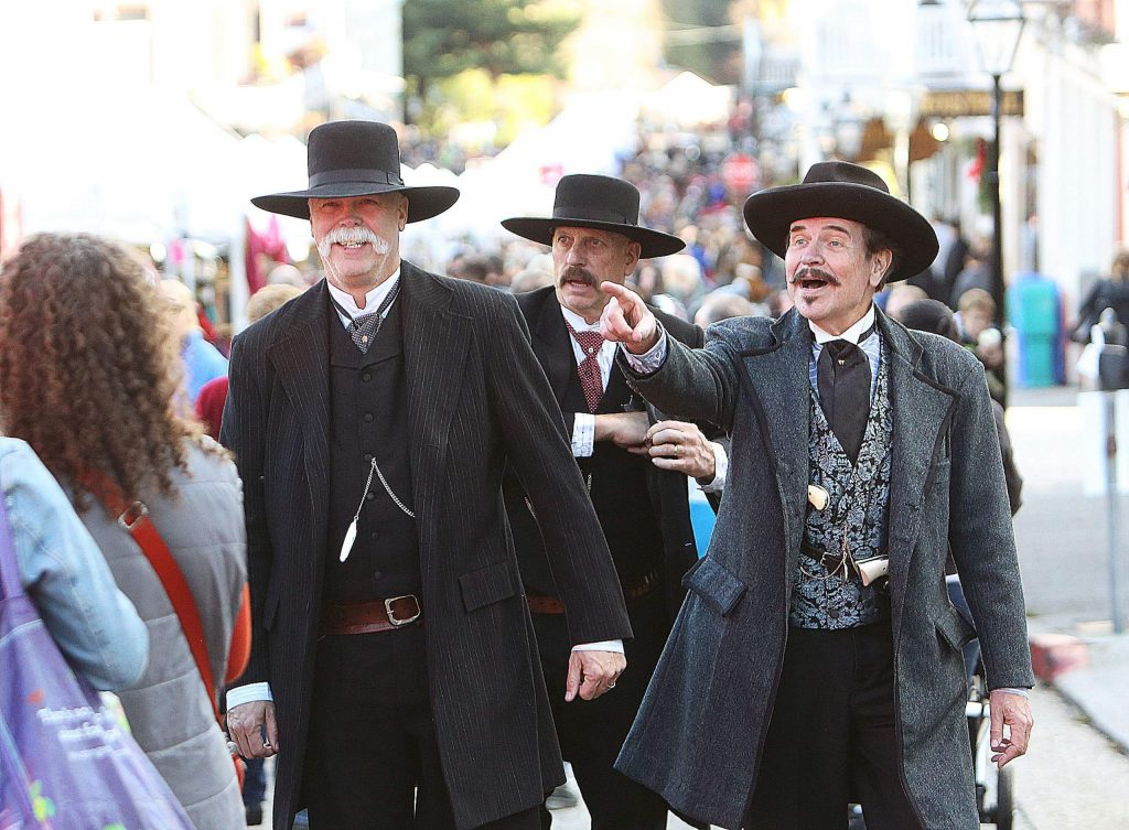 History buffs portraying Tombstone the movie characters' Virgil (Larry Ford), Wyatt Earp (Tom Dragt), and Doc Holliday (Mike Melius) approach the top of Broad Street for their annual group photo.