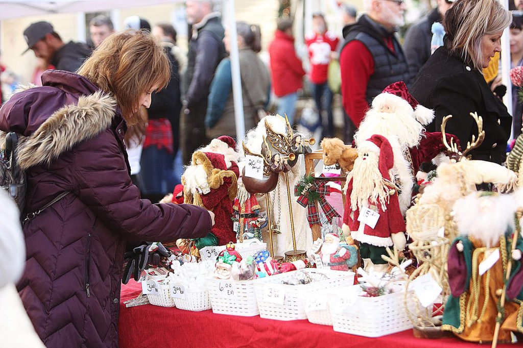 A craft faire shopper looks at Christmas collectibles offered by Collectibles Unlimited Sunday at Victorian Christmas.
