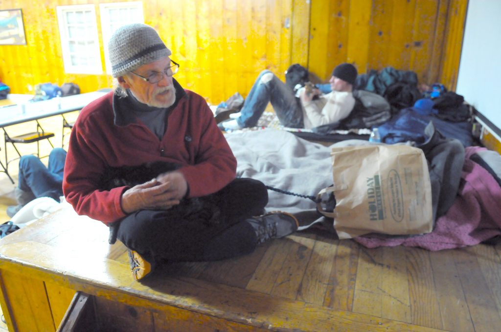 FILE - Chuck Farnsworth, 63, and his cat Takeo, bed down at the warming shelter run by Sierra Roots in Nevada City on Christmas evening in 2016.