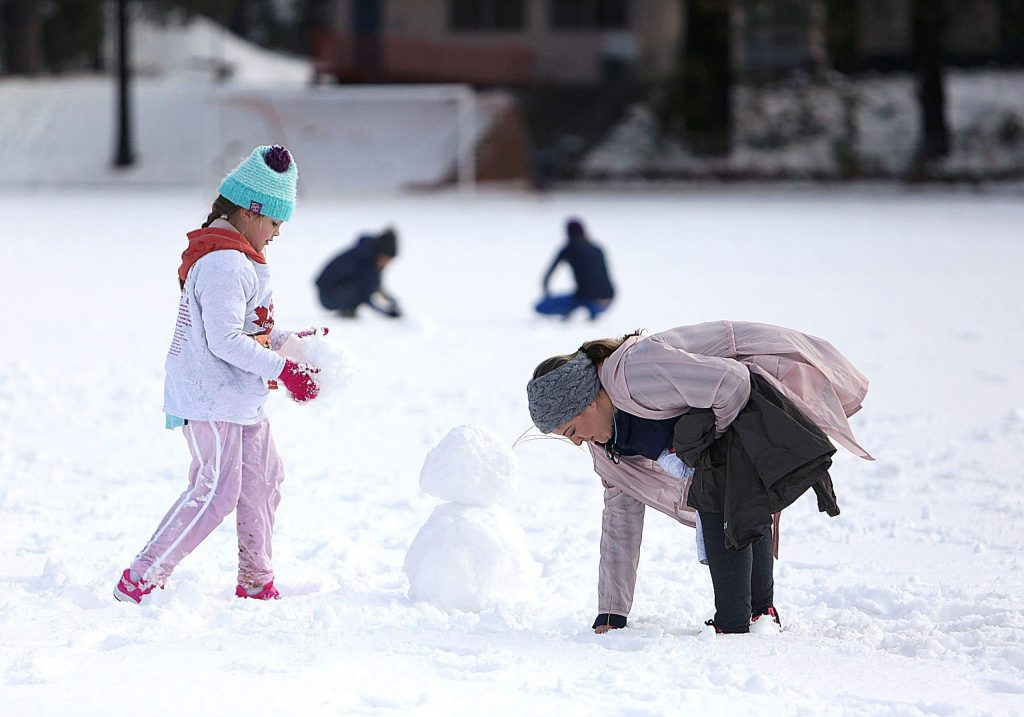 Mother and daughter Elaine Cummings and Aurora (9) make a snowman on the football field of Nevada Union High School after late November's low snow.