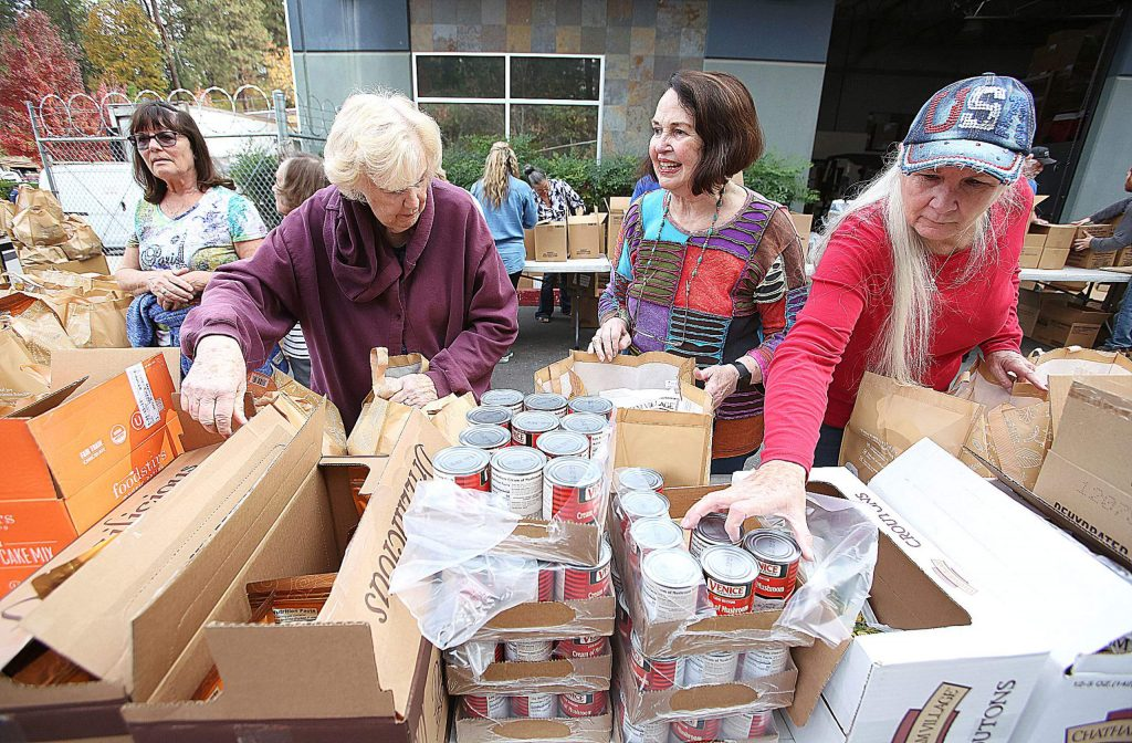 Rotary of Grass Valley's Chris Parks, center, pauses to share a smile Tuesday morning while flanked by regular food bank volunteers MaryAnn Davis, left, and Donna Ruiz, right as they prepare the Food Bank of Nevada County holiday food baskets.