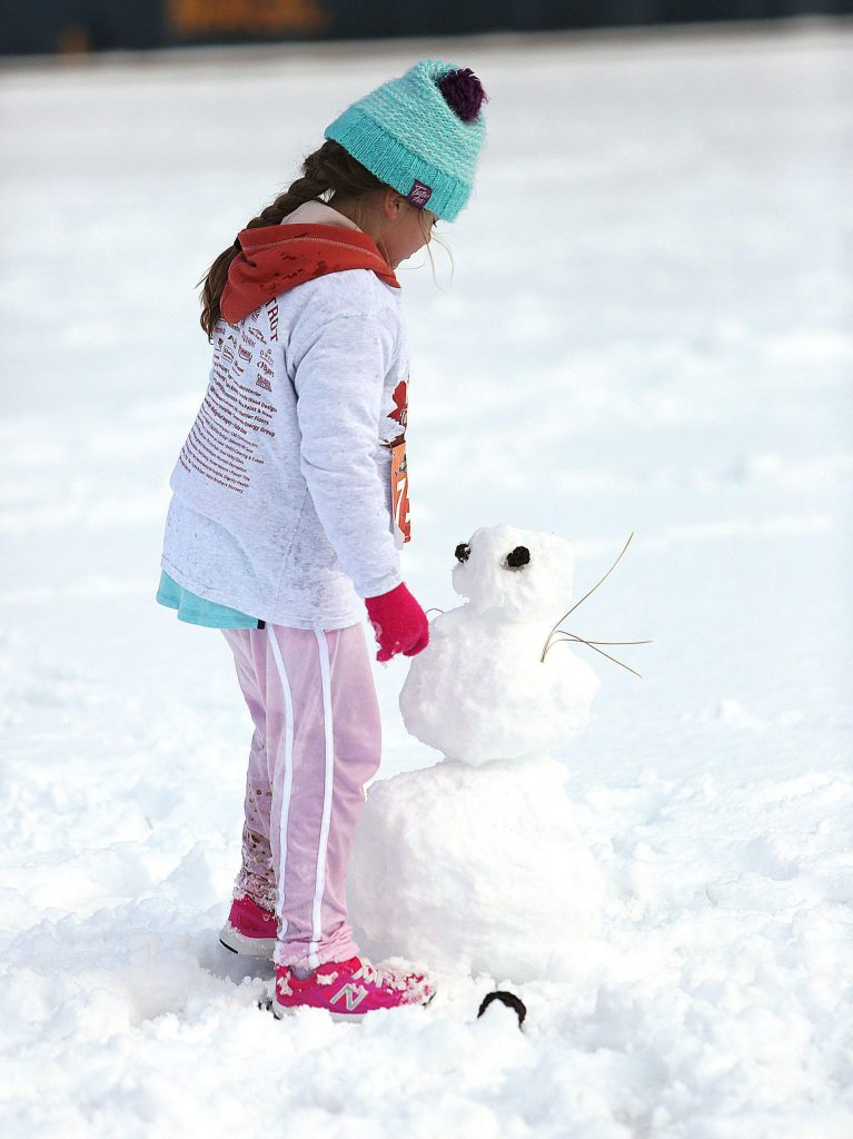 Nine year old Aurora Cummings takes a look at her snowman as his face begins to take shape Thanksgiving morning at Nevada Union High School.