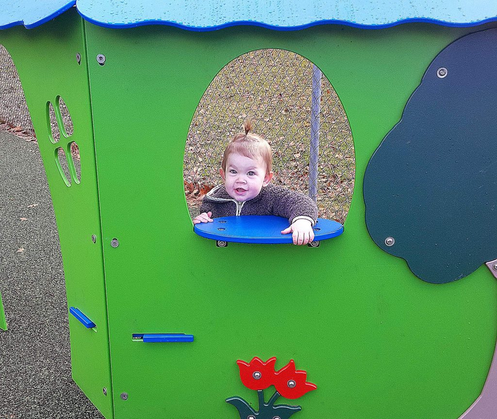 Nova Rose Holden, 19 months, peeks out from the window of a wooden playhouse at Memorial Park Monday.
