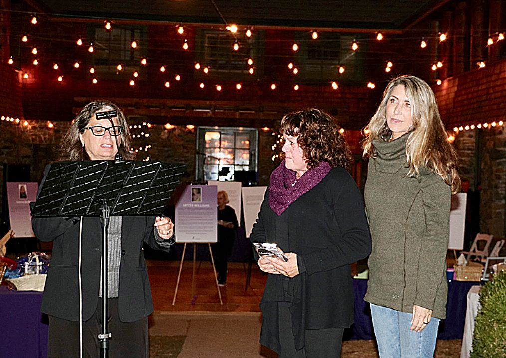 Nevada County Supervisor Heidi Hall reads from a certificate of appreciation by the Board of Supervisors, thanking WoW founder Sandy Escobar for her 20 years of service to the community. Standing next to Sandy is Katy Jacobs, former Assistant District Attorney who prosecuted the Hetty Williams murder case. Hetty is the namesake of Hetty's Haven, WoW's transitional shelter. Katy also presented Sandy with an award for service to the community.