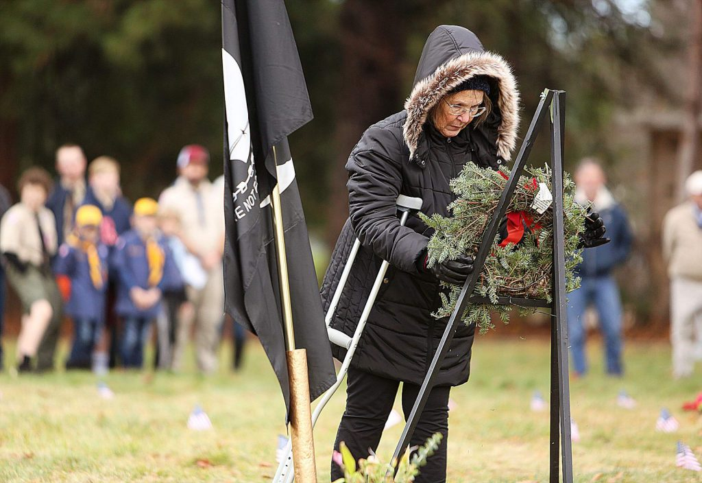 Gold Star Mother Jeannie Lawrence places a wreath to honor the U.S. POW's/MIA during Saturday's Wreaths Across America ceremony.