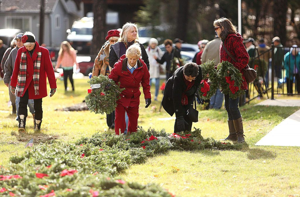 Community members pick up wreaths to be placed on the graves of veterans at St. Patrick's Cemetery during Saturday's Wreaths Across America ceremony.