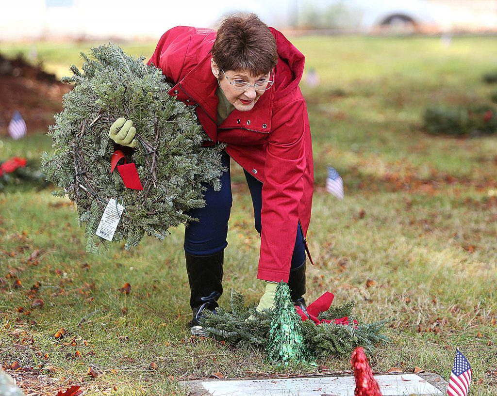 Daughters of the American Revolution's Bev Erickson places wreaths on the graves of veterans Saturday at St. Patrick's Cemetery in Grass Valley.