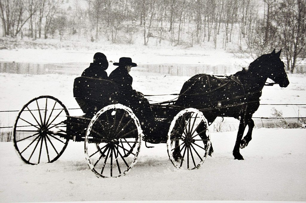 One of Ron Berkheimer's favorite pictures shows an Amish couple riding in an open buggy through a snow-covered and snowing landscape.
