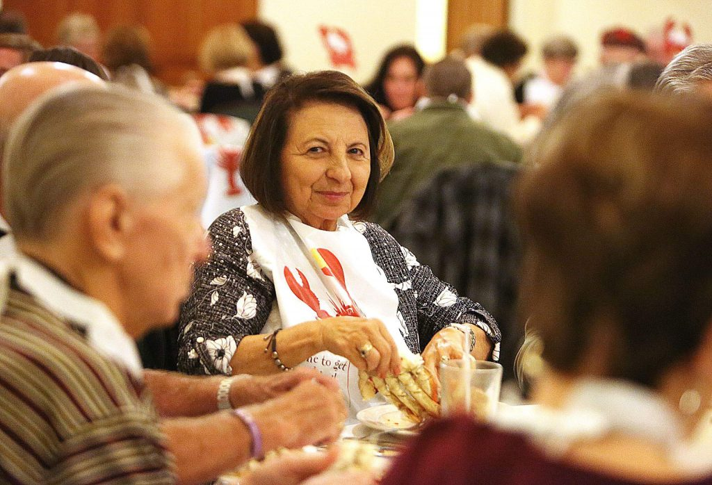Diana Garbin smiles as she readies to crack open her first crab legs of the evening Saturday at the Alta Sierra Country Club.