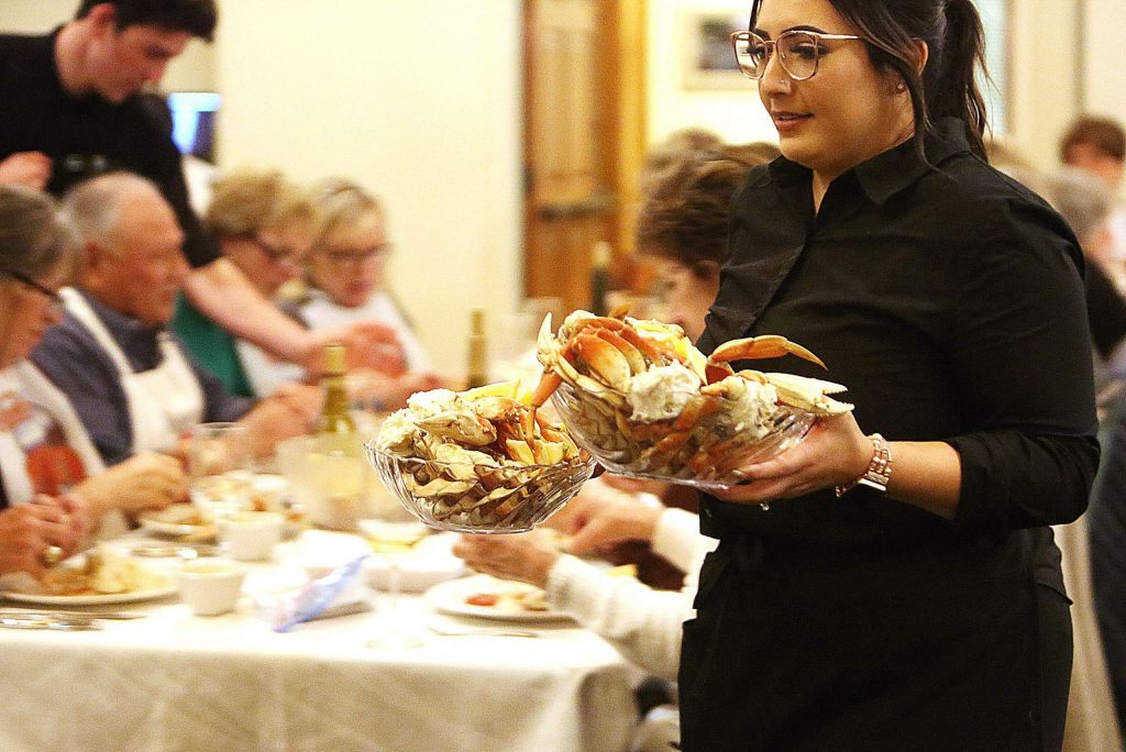 Country Club waitress Maria Nolen carries out another round of the all you can eat crab dinner.