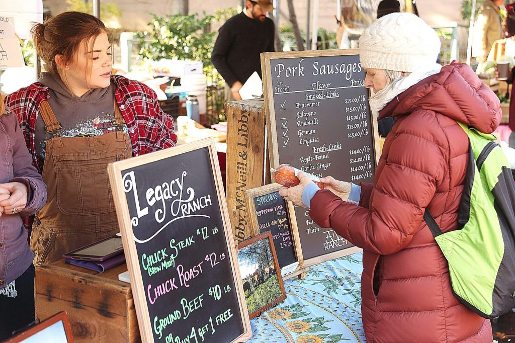 AM Ranch intern Anna Raymond helps a customer with a purchase of Spanish style chorizo during Saturday's Nevada City Farmers Market. AM Ranch pork are all pasture raised and supplemented with a non GMO feed and forage crop out of Penn Valley.