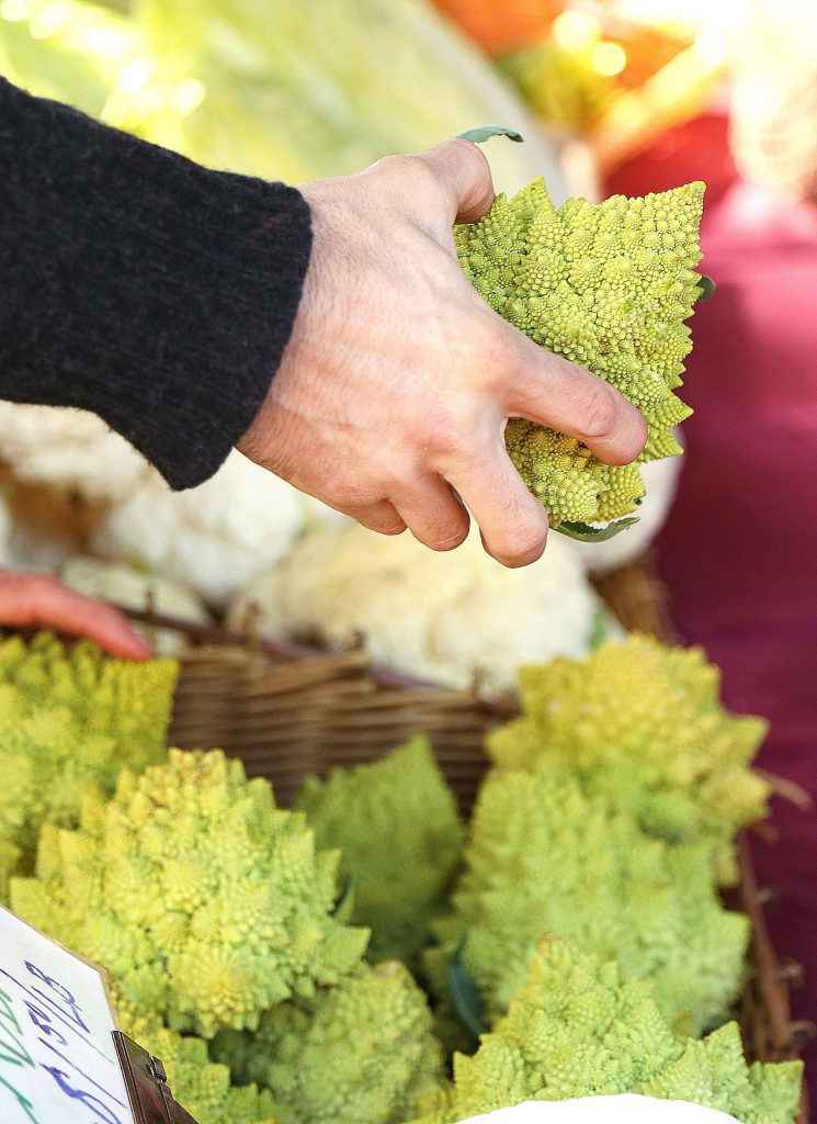 A Romanesco is offered to a customer by Riverhill Farms during the first Nevada City Farmer's Market of the year Saturday in the Three Forks parking lot.