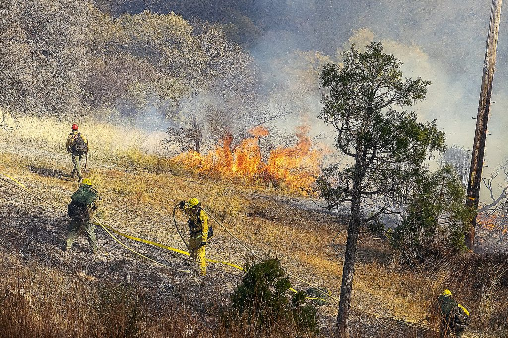A firefighter puts water on a hot spot at the vegetation fire that broke out on Sutton Way at Dorsey Drive, Grass Valley, on Oct. 27 in this archive photo. Fire crews from Grass Valley, Nevada City, Nevada County Consolidated, Cal Fire, Tahoe National Forest, Ophir Hill and Chicago Park, as well as crews from the Washington and Deadwood conservation camps, responded to the blaze.