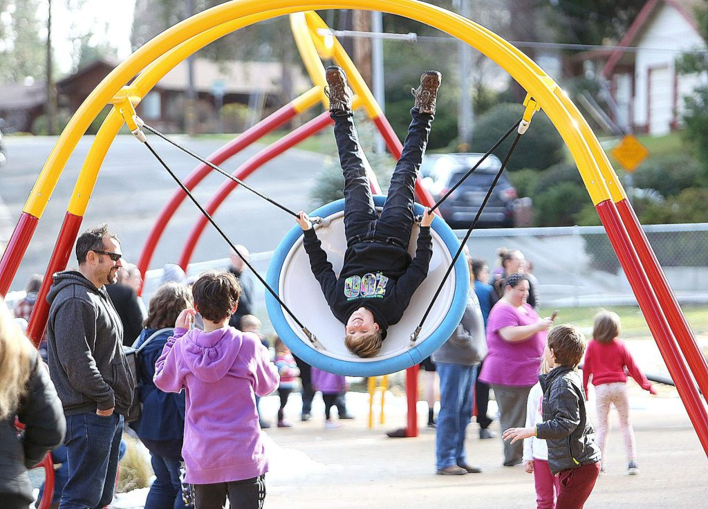 Grass Valley's Kade Allen-Burr gets un upside down perspective on the new playground structures at the recently opened Minnie Park at Minnie and Butler Streets in downtown Grass Valley.